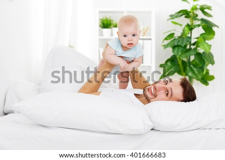happy family father and baby playing on bed