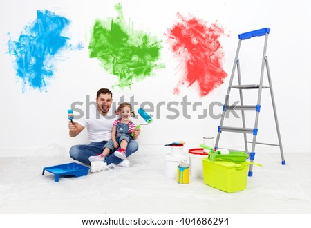 happy family father and child daughter making repairs, paint the wall at home - stock photo