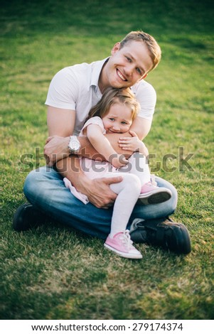Happy family. Father and daughter bonding to each other outside on grass - stock photo