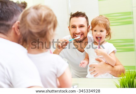 Happy family father and daughter child girl brushing her teeth in the bathroom toothbrushes - stock photo