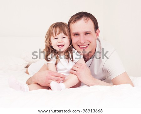 happy family,  father and daughter embracing and laughing in bed at home - stock photo