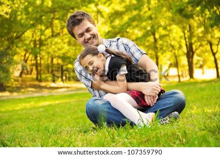 Happy family, father and doghter have fun in the park