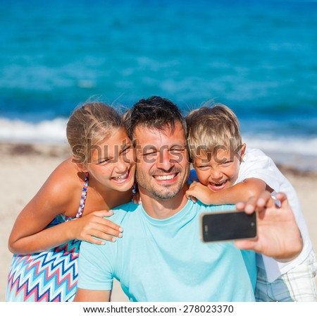 Happy family father and his adorable kids at beach taking selfie - stock photo