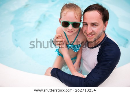Happy family father and his adorable little daughter at outdoors swimming pool - stock photo