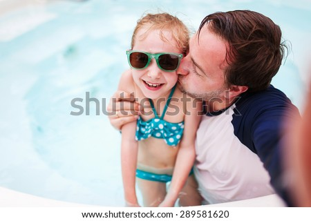 Happy family father and his adorable little daughter at outdoors swimming pool making selfie - stock photo