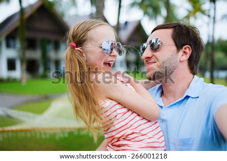 Happy family father and his adorable little daughter on vacation taking selfie - stock photo