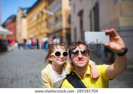 Happy family father and his adorable little daughter taking selfie with mobile phone outdoors at street of Stockholm, Europe - stock photo