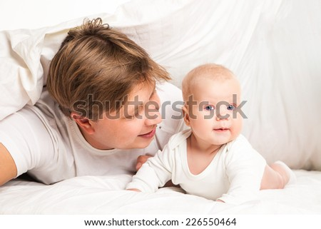 happy family, father and his baby under the blanket on the bed at home - stock photo