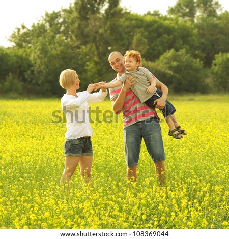 happy family. father and mother holding son in their hands in the field of yellow flowers. outdoor shot - stock photo