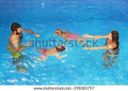 Happy family - father and mother in blue pool with babies girl and boy swimming underwater with fun. Healthy lifestyle, active parents and people water sports lessons on summer vacation with children