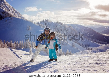 Happy family, father and son, in winter clothing at the ski resort, winter time, on top of a mountain, ready to ski - stock photo