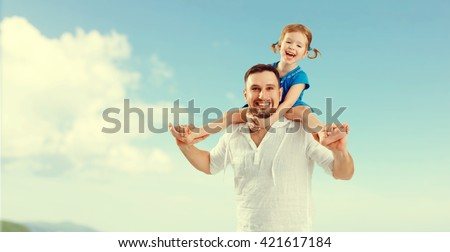 happy family father  day. father  and child daughter playing and having fun in sky - stock photo