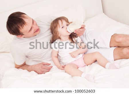 happy family;  father feeding his daughter with milk  in bed at home