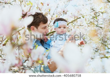 Happy family. Father holds a child in the blooming apple trees, on sunny day in the park. Positive human emotions, feelings. Cherry and apple blossom. Spring time. outdoors. Father and baby daughter - stock photo