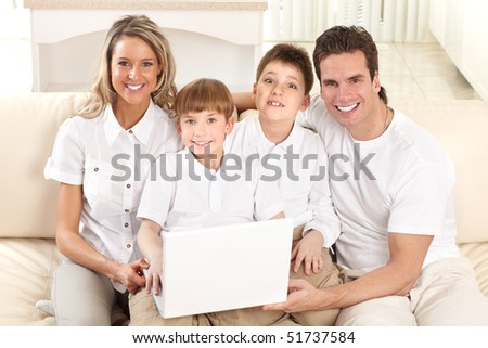 Happy family. Father, mother and boy working with laptop.