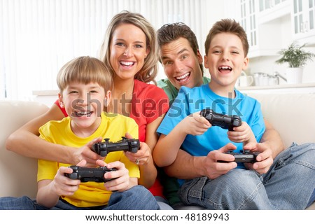 Happy family. Father, mother and children playing a video game