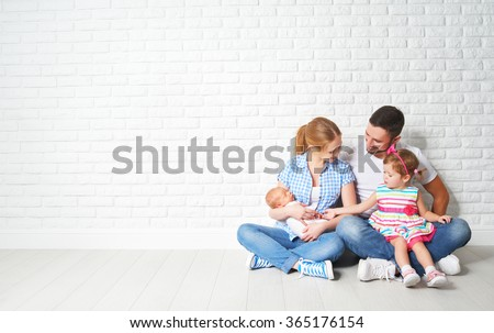 happy family father mother and children sitting on the floor in an empty brick wall - stock photo
