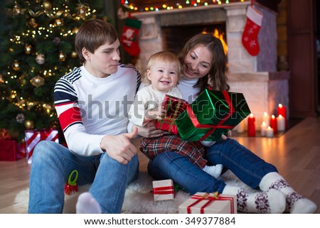Happy family - father, mother and little son sitting with gifts near Christmas tree and fireplace