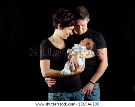 Happy family, father, mother and newborn baby. - stock photo