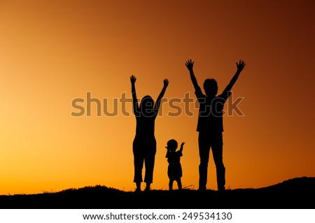 Happy family father mother and son playing outdoors at sunset silhouette