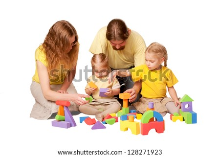 Happy family, father, mother and two children building from toy blocks. Isolated on white background