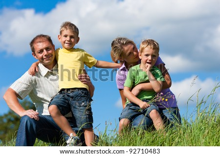 Happy family (father, mother and two sons) in summer in front of a blue sky