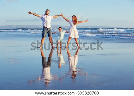 Happy family - father, mother, baby son walk with fun along edge of sunset sea surf on black sand beach. Active parents and people outdoor activity on summer vacations with children on Bali island - stock photo