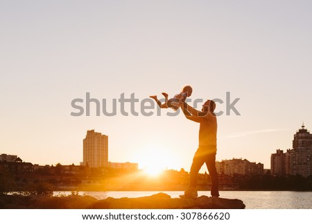 Happy family. Father with little child at sunset - stock photo
