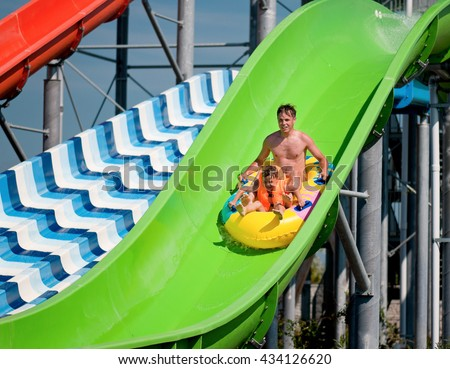 Happy family - father with son - having fun water sliding at aqua park - stock photo