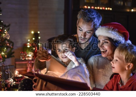 happy family finds a digital tablet in a gift on the Christmas night,  near the wood stove and lit Christmas tree in their living room, the mother wears a santa hat - stock photo