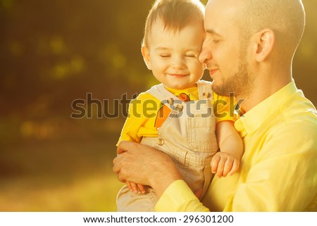 Happy family, friends forever concept. Smiling father and little son walking together in a park. Dad holding baby. Sunny summer day. Close up. Copy-space. Outdoor shot