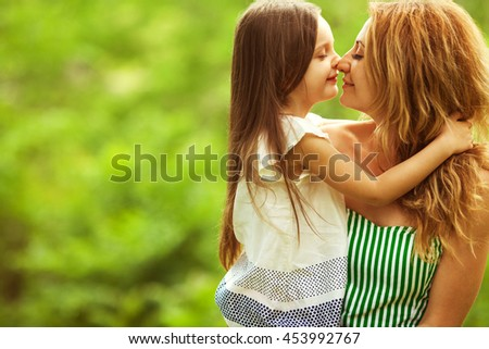Happy family, friends forever concept. Smiling mother and little daughter walking together in a park. Mom holding baby. Sunny summer day. Close up. Copy-space. Outdoor shot