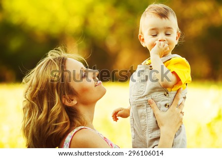 Happy family, friends forever concept. Smiling mother and little son playing together in a park. Mum holding shy baby. Sunny windy summer day. Close up. Copy-space. Outdoor shot