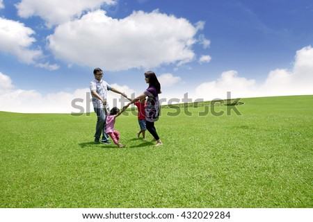 Happy family gathering in the park under blue sky - stock photo