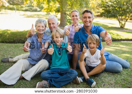 Happy family gesturing thumbs up in the park on a sunny day - stock photo