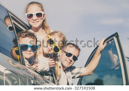 Happy family getting ready for road trip on a sunny day.  Concept of friendly family.