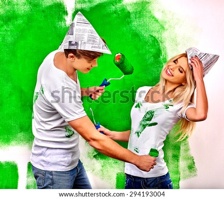 Happy family girl and man paint wall at home. - stock photo