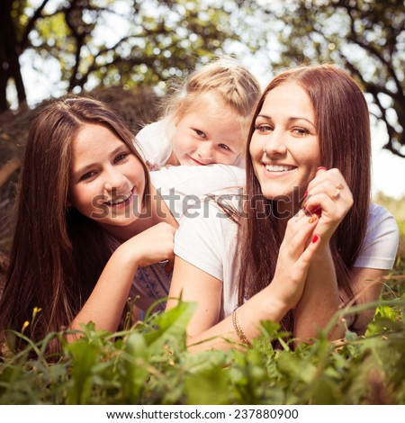 happy family girlfriends having fun lying on the green park outside - stock photo
