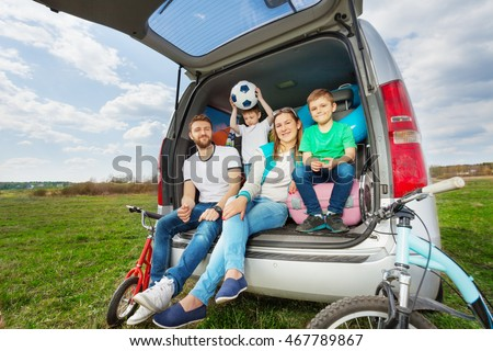 Happy family going for a car trip in summer