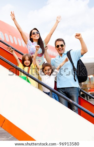 Happy family going on holidays and getting on the airplane - stock photo