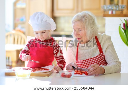 Happy family, grandmother and granddaughter, adorable little girl, preparing delicious pizza together topping it with tomato sauce, vegetables and cheese, sitting at table at bright sunny room at home - stock photo