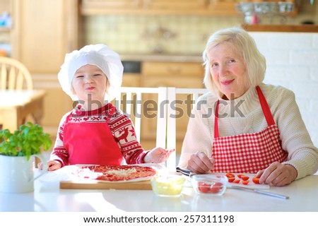 Happy family, grandmother with her granddaughter, adorable little girl, preparing delicious pizza together topping it with tomato sauce, vegetables and cheese. Selective focus on child - stock photo