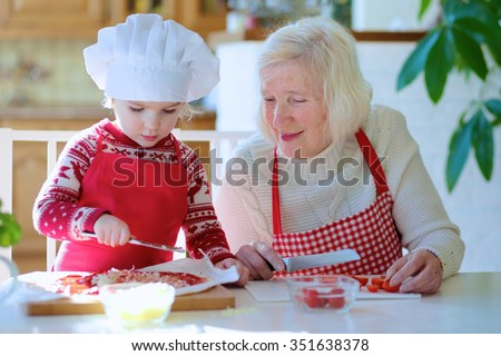 Happy family, grandmother with little granddaughter, preparing pizza together topping it with tomato sauce, vegetables and cheese, sitting at white dining table in bright sunny room. Focus on child. - stock photo