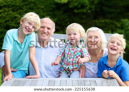Happy family, grandparents with three grandchildren, relaxing together in the garden sitting at wooden picnic table - stock photo