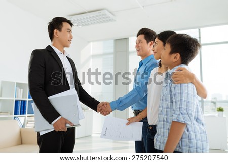 Happy family greeting real estate agent