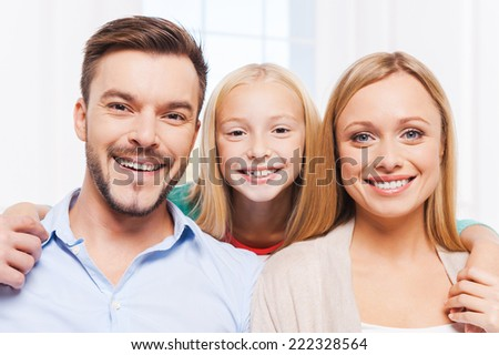 Happy family. Happy family of three bonding to each other and smiling while sitting indoors  - stock photo