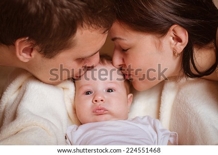 happy family. happy young parents kissing their baby - stock photo