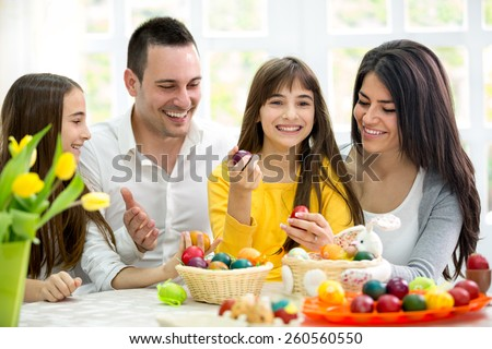 Happy family have fun with Easter eggs, together on holiday - stock photo