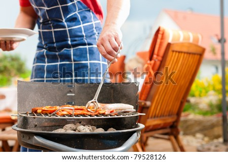 Happy family having a barbecue in summer; father stands next to the fire - stock photo