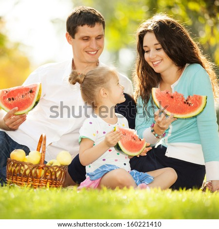Happy family having a picnic in the autumn garden - stock photo